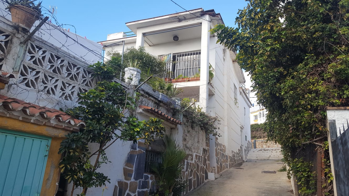 This spacious detached house is located in Montemar, just a 5 minute walk from the popular La Carihuela beach in Torremolinos. The house needs to be fully reformed. It currently has 5 bedrooms, 3 bedrooms, several terraces, a sunny garden and a large roof terrace with beautiful sea views. The lay out can stay as it is but you could also convert it into 3 self-contained apartments with separate entrances. You could even add an extra floor. A perfect investment opportunity if you want to own a villa close to the beach or if you are looking for a property which can be used as a (holiday) rental.